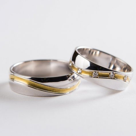 Elegante Trauringe aus Weißgold mit einem wellenförmigem Schlitz um den Umkreis mit Gelbgold ausgelegt